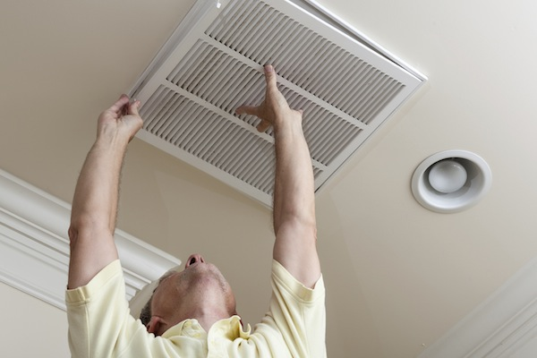 Senior man opening air conditioning filter in ceiling